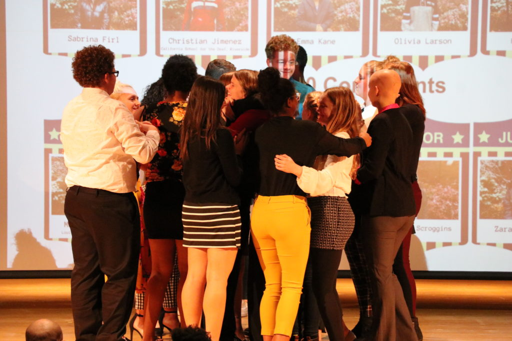 Contestants are hugging each other.